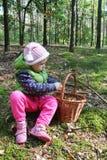Dois anos de menina idosa com uma cesta completa dos cogumelos Fotos de Stock