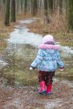 Dois anos de menina idosa que anda na poça gelada Imagens de Stock Royalty Free