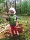 Dois anos de menina idosa que encontra cogumelos em uma floresta Fotografia de Stock Royalty Free