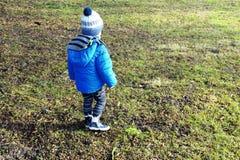 Dois anos de menino idoso que anda em torno da jarda imagens de stock
