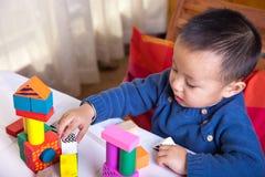 Dois anos de menino que joga com blocos de madeira. Fotos de Stock Royalty Free