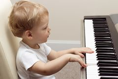 Dois anos louros bonitos da criança que joga no piano eletrônico Imagens de Stock Royalty Free