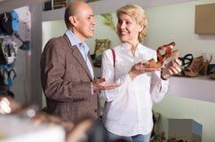 Dois aposentados que escolhem junto pares de sapatas na loja da forma Fotografia de Stock Royalty Free