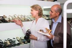Dois aposentados que escolhem junto pares de sapatas na loja da forma Fotografia de Stock