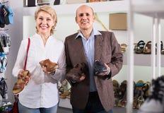 Dois aposentados que escolhem junto pares de sapatas na loja da forma Fotos de Stock