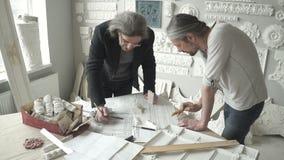 Dois arquitetos masculinos maduros que estão na tabela video estoque