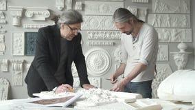 Dois arquitetos masculinos que escolhem o molde para a fachada filme