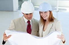 Dois arquitetos que discutem uma planta da construção Fotografia de Stock Royalty Free