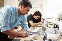 Dois arquitetos que fazem modelos no escritório usando a tabuleta de Digitas Imagens de Stock