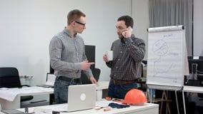 Dois arquitetos que têm o telefonema durante a ruptura de café foto de stock royalty free