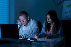 Dois arquitetos que trabalham na noite imagem de stock