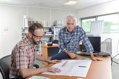 Dois arquitetos recolhidos em torno dos planos imagem de stock