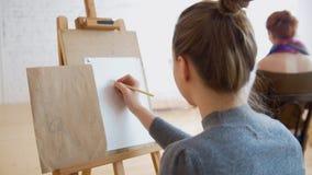 Dois artistas fêmeas que esboçam o modelo na classe de desenho brilhante foto de stock royalty free