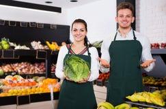 Dois assistentes novos que indicam vegetais fotos de stock royalty free