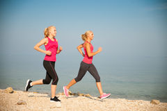 Dois athlets que correm na praia - verão w das mulheres do amanhecer Imagens de Stock