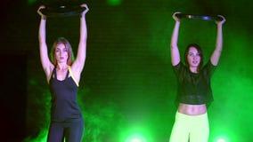 Dois atléticos, bonito, as mulheres que fazem a força exercitam com placas pesadas, na noite, no fumo claro, névoa, dentro video estoque