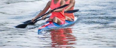 Dois atletas da jovem mulher em enfileirar o caiaque no lago durante a competição foto de stock