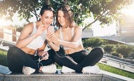 Dois atletas das jovens mulheres no sportswear estão sentando-se no parque, relaxam após esportes treinando, usam o smartphone fotografia de stock