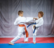 Dois atletas pequenos estão treinando o karaté emparelhado dos exercícios foto de stock