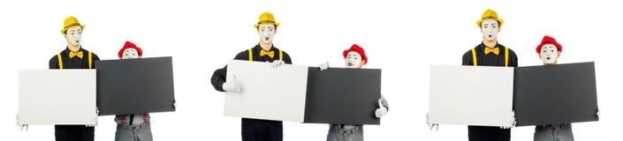 Dois atores, pantomimas, guardam formulários vazios para o texto Isolado no branco fotografia de stock royalty free