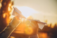 Dois aviões de papel nas mãos que olham se no por do sol Imagem de Stock Royalty Free