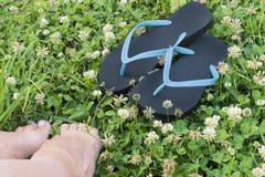 Dois azuis e flip-flops pretos e pés colhidos da mulher no prado verde fotografia de stock