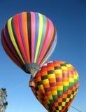 Dois balões de ar quente coloridos em um céu azul imagem de stock