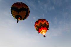 Dois balões de ar quente coloridos flutuam afastado no céu azul Fotografia de Stock Royalty Free