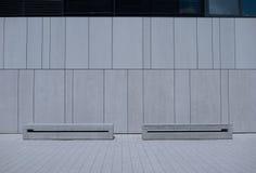 Dois bancos similares contra a parede branca da construção Foto de Stock