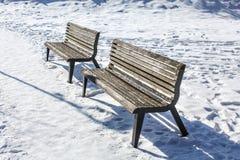 Dois bancos vazios em coberto de neve imagens de stock