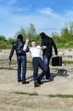 Dois bandidos sequestraram um homem de negócios Fotografia de Stock Royalty Free