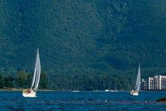 Dois barcos de vela no lago pela montanha imagem de stock