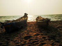 Dois barcos na costa de mar do mar árabe durante o por do sol na costa de kerala fotografia de stock royalty free