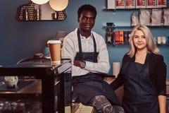 Dois baristas multirraciais novos nos aventais que estão welcomingly em sua cafetaria na moda imagens de stock royalty free