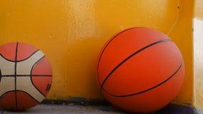 Dois basquetebol que encontram-se sob a parede amarela Imagens de Stock Royalty Free