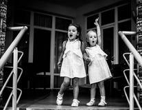 Dois bebês das irmãs no mesmos vestem-se, guardando as mãos Pequim, foto preto e branco de China Foto de Stock Royalty Free