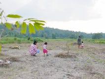 Dois bebês pequenos junto com sua avó, e mãe que passa o tempo exterior em um campo aberto natural imagem de stock