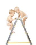 Dois bebês que escalam e que lutam no stepladder Imagens de Stock