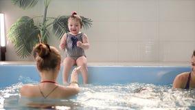 Dois bebês riem na associação e no salto na água que aplaude suas mãos vídeos de arquivo
