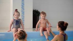 Dois bebês riem na associação e no salto na água que aplaude suas mãos filme