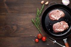 Dois bifes crus na frigideira no fundo de madeira rústico Partes de carne prontas para cozinhar Imagem de Stock Royalty Free
