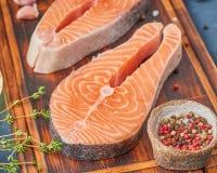 Dois bifes de salmões, peixes enfaixam, grandes parcelas cortadas em uma placa de desbastamento na tabela escura Fundo do aliment foto de stock royalty free