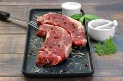 Dois bifes de tira crus da carne em um prato preto da preparação Foco seletivo Imagem de Stock
