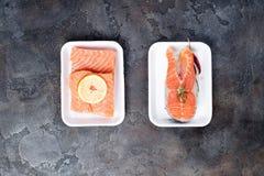 Dois bifes salmon crus frescos estão colocando na bandeja branca do alimento feita da espuma de poliestireno imagem de stock