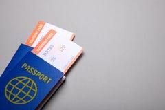 Dois bilhetes para o avião com os passaportes no fundo cinzento Copie o espaço para o texto Fotos de Stock Royalty Free