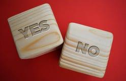 Dois blocos de madeira com palavras: sim-não no fundo vermelho imagem de stock royalty free