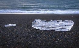 Dois blocos transparentes de mentira do gelo na praia preta de Islândia nas costas do Oceano Atlântico fotos de stock