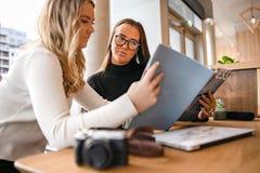 Dois Bloggers novos sérios que discutem sobre a publicação no café foto de stock royalty free