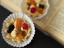 Dois bolos com creme da manteiga e fruto do chá no livro aberto imagem de stock royalty free