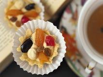 Dois bolos com creme e fruto da manteiga perto de um copo do chá no livro aberto imagens de stock royalty free